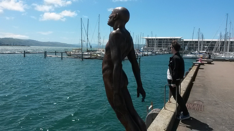 Dan braces himself from the wind along the harbour next to a very silent man.